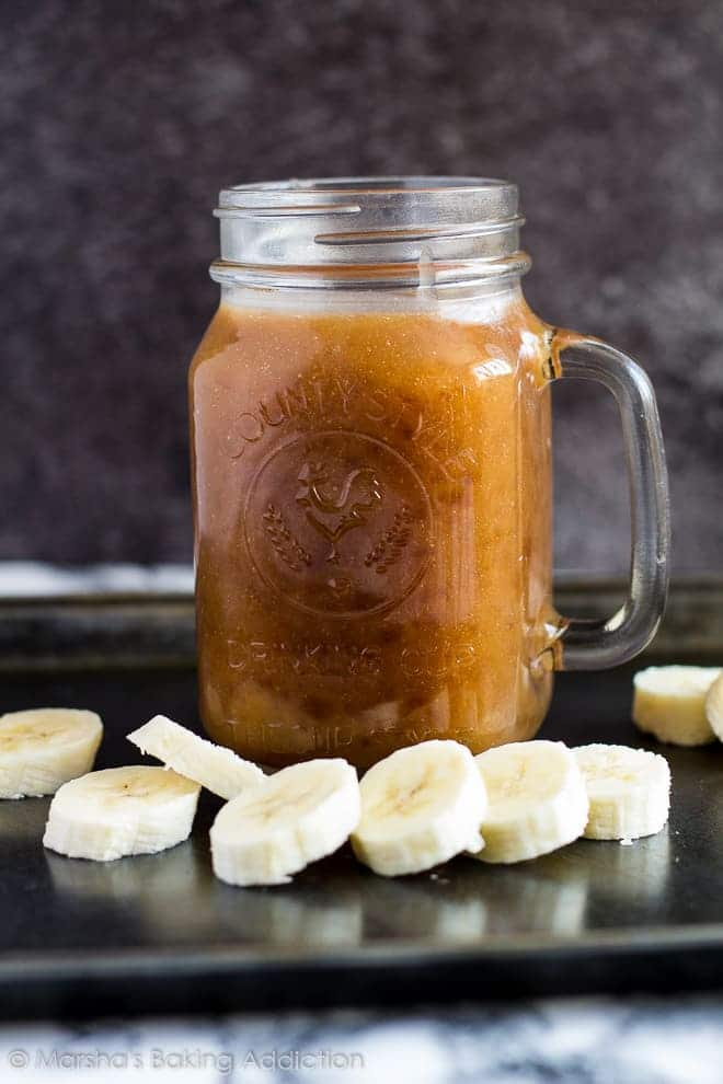 A mason jar filled with banana caramel sauce on a baking tray with a row of banana slices.