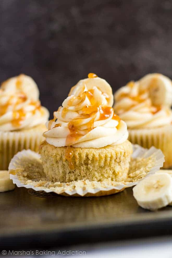 Frosted banana caramel cupcakes on a baking tray with the wrapper peeled off.