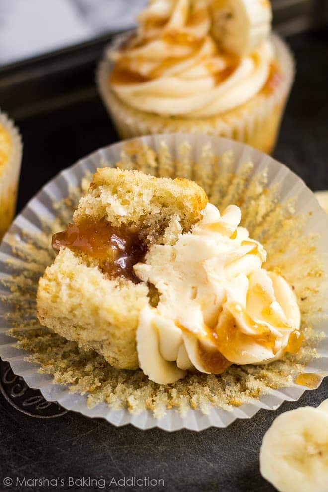Overhead shot of frosted banana caramel cupcakes with a bite taken out of it to show caramel filling.