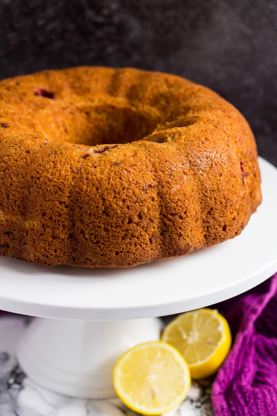 Unfrosted lemon raspberry bundt cake on a white cake stand.