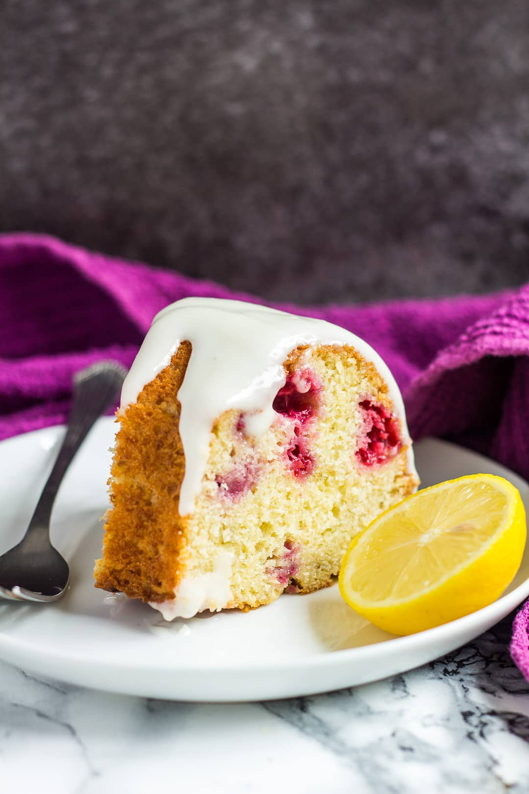 A slice of lemon raspberry bundt cake on a small white plate with a fork.
