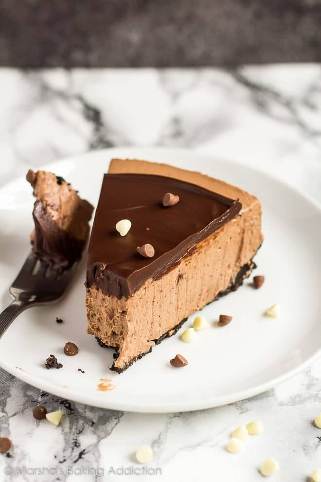 A slice of no-bake double chocolate cheesecake served on a small white plate with a fork.