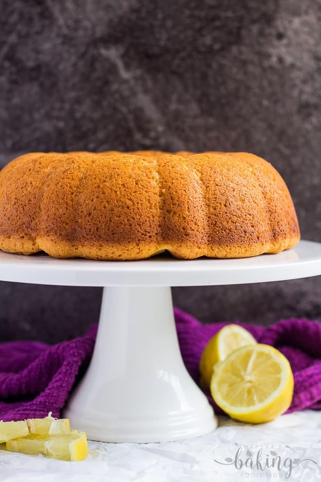 A cheesecake swirl lemon bundt cake with no glaze on a white cake stand.