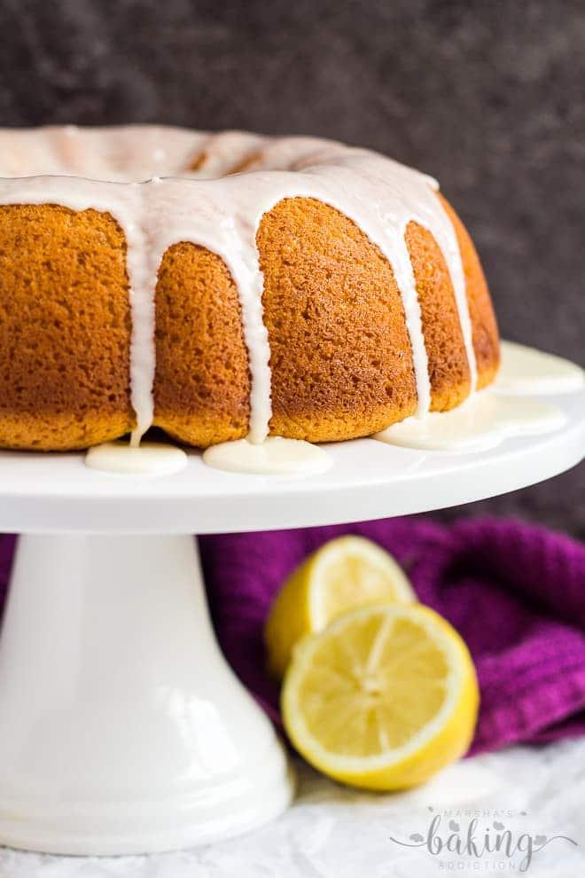 A glazed cheesecake swirl lemon bundt cake on a white cake stand.