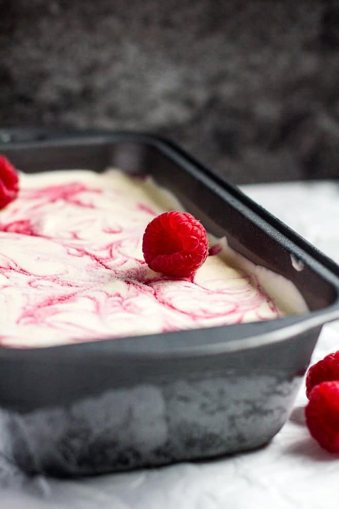 Raspberry ripple ice cream in a loaf pan on parchment paper.