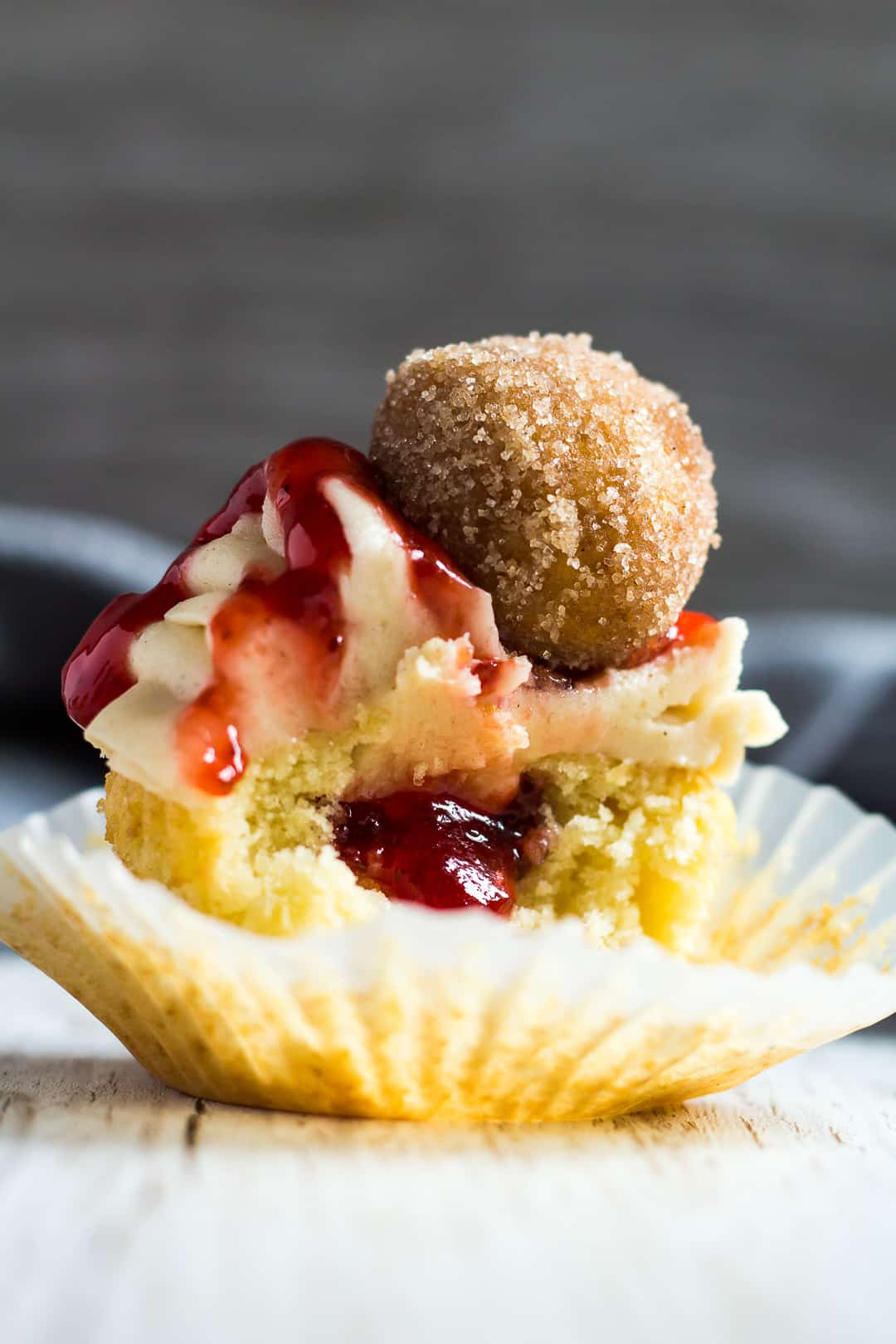A Jam Doughnut Cupcake cut in half in its wrapped to show jam filling.