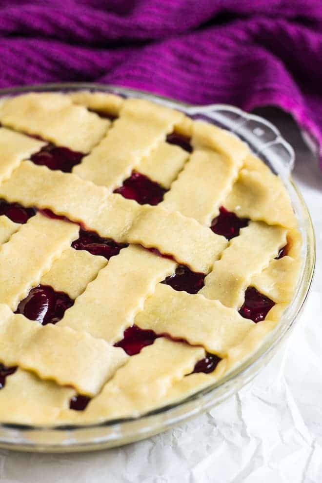 Homemade cherry filling sealed inside a pie crust with a lattice top in a glass pie dish.