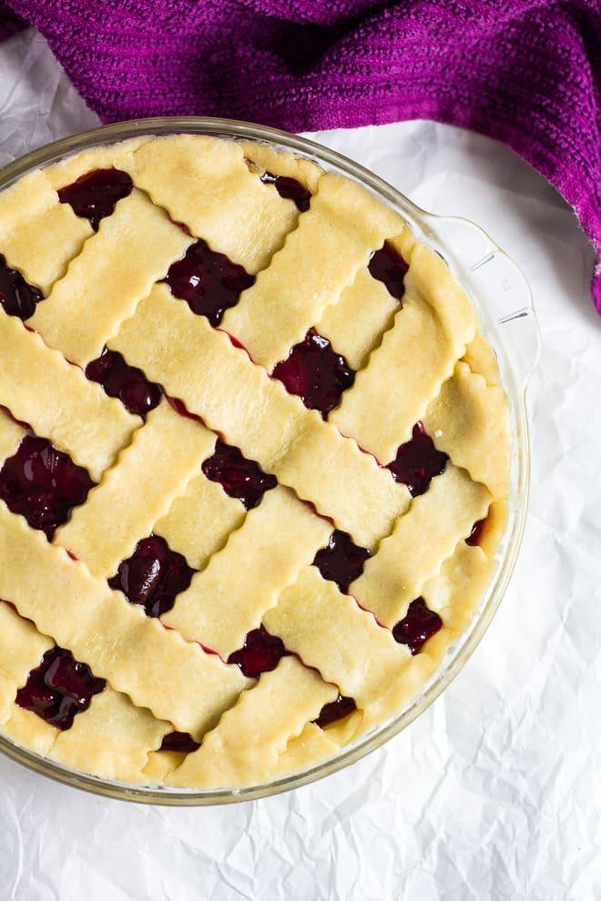 Overhead shot of lattice pie crust top on homemade cherry pie before baking.