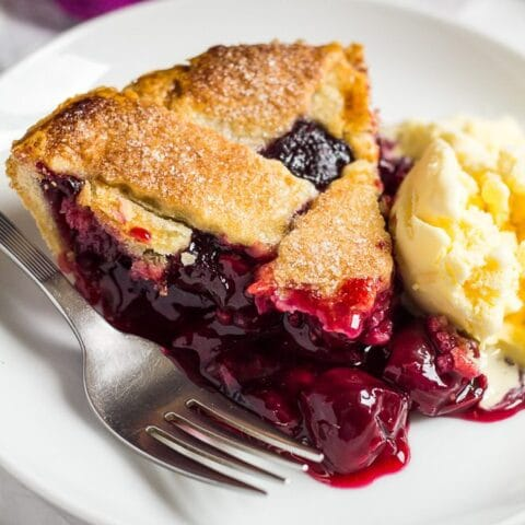 Slice of homemade cherry pie on a small white plate with a scoop of ice cream and a fork.