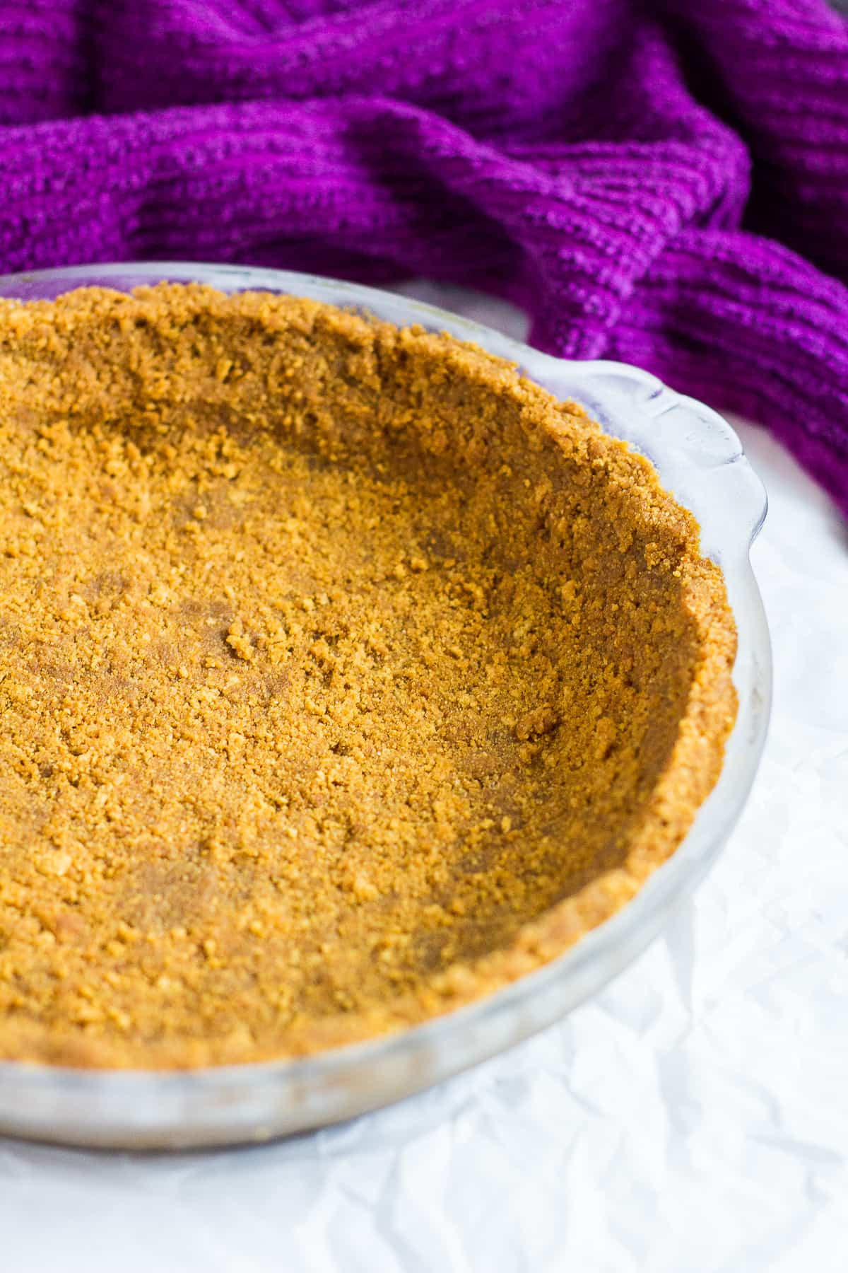 Ginger biscuit crust in a glass pie dish for no-bake key lime pie.