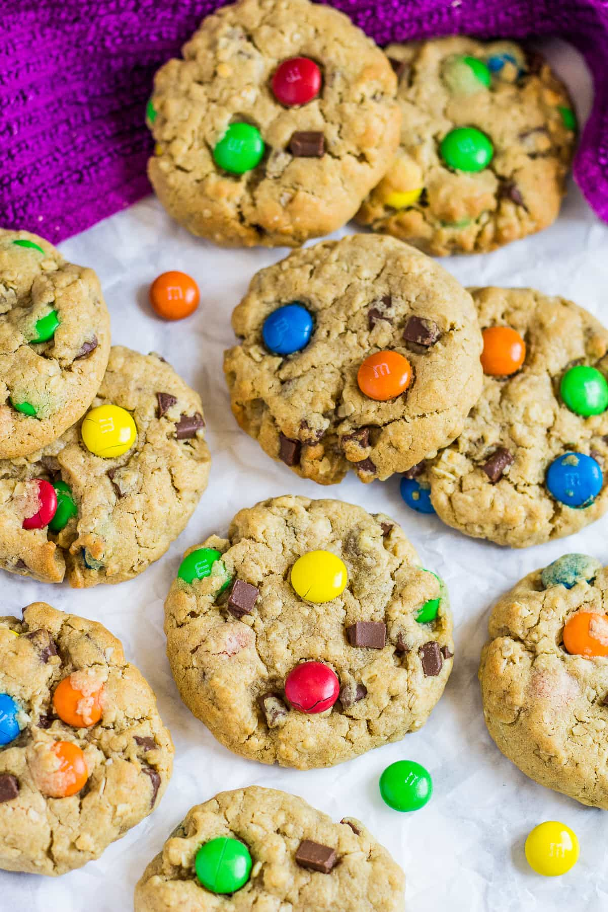 Overhead shot of monster cookies with M&Ms on parchment paper.