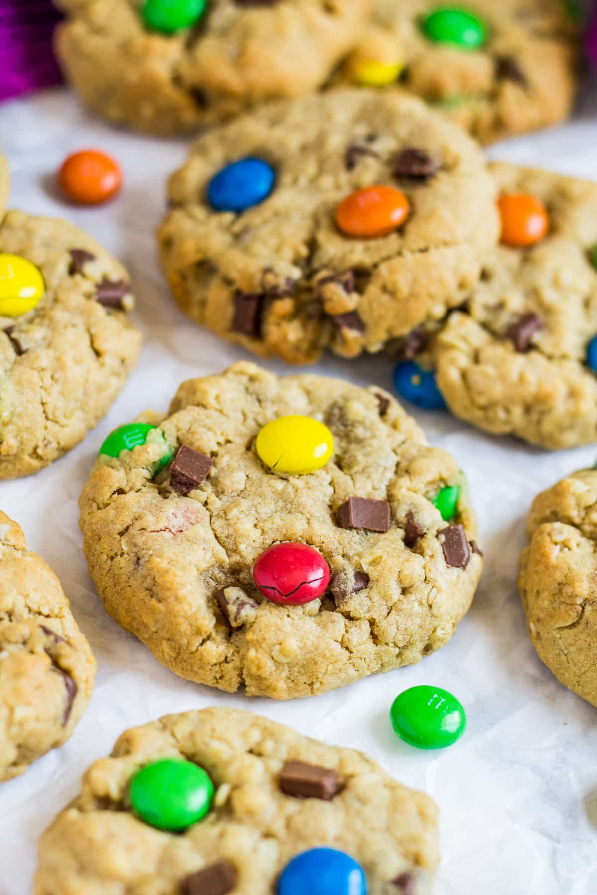 Monster cookies with M&Ms on parchment paper.