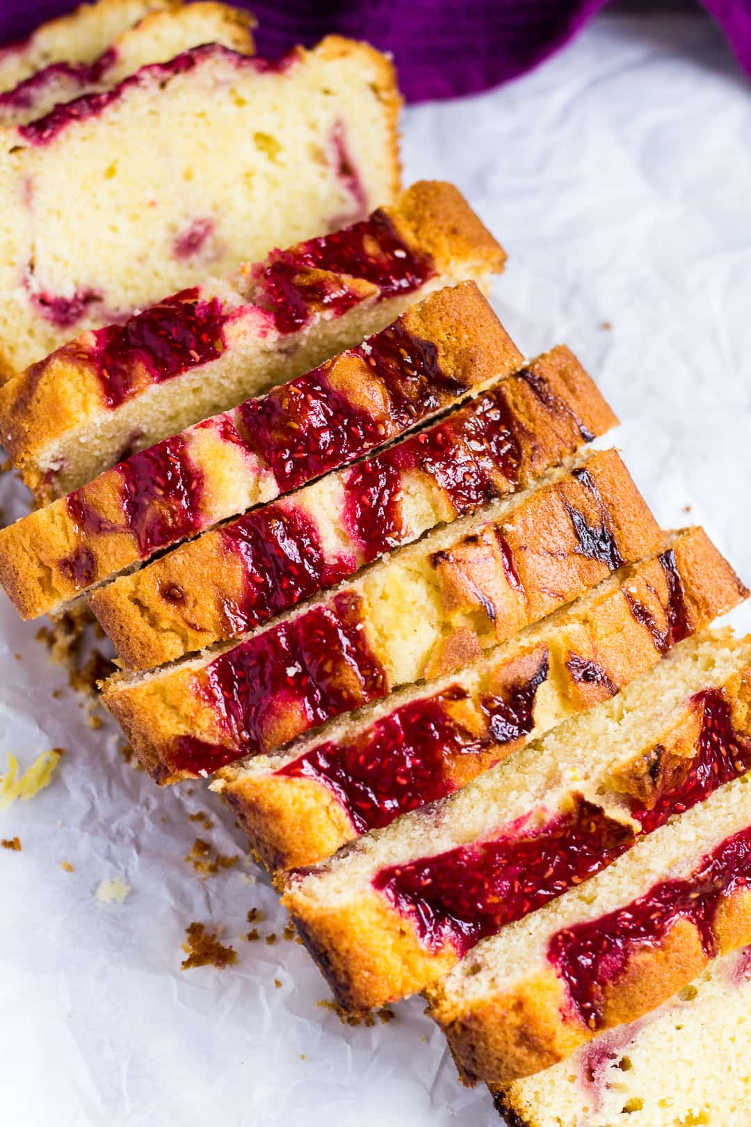 Overhead shot of raspberry swirl lemon pound cake cut into slices on parchment paper.