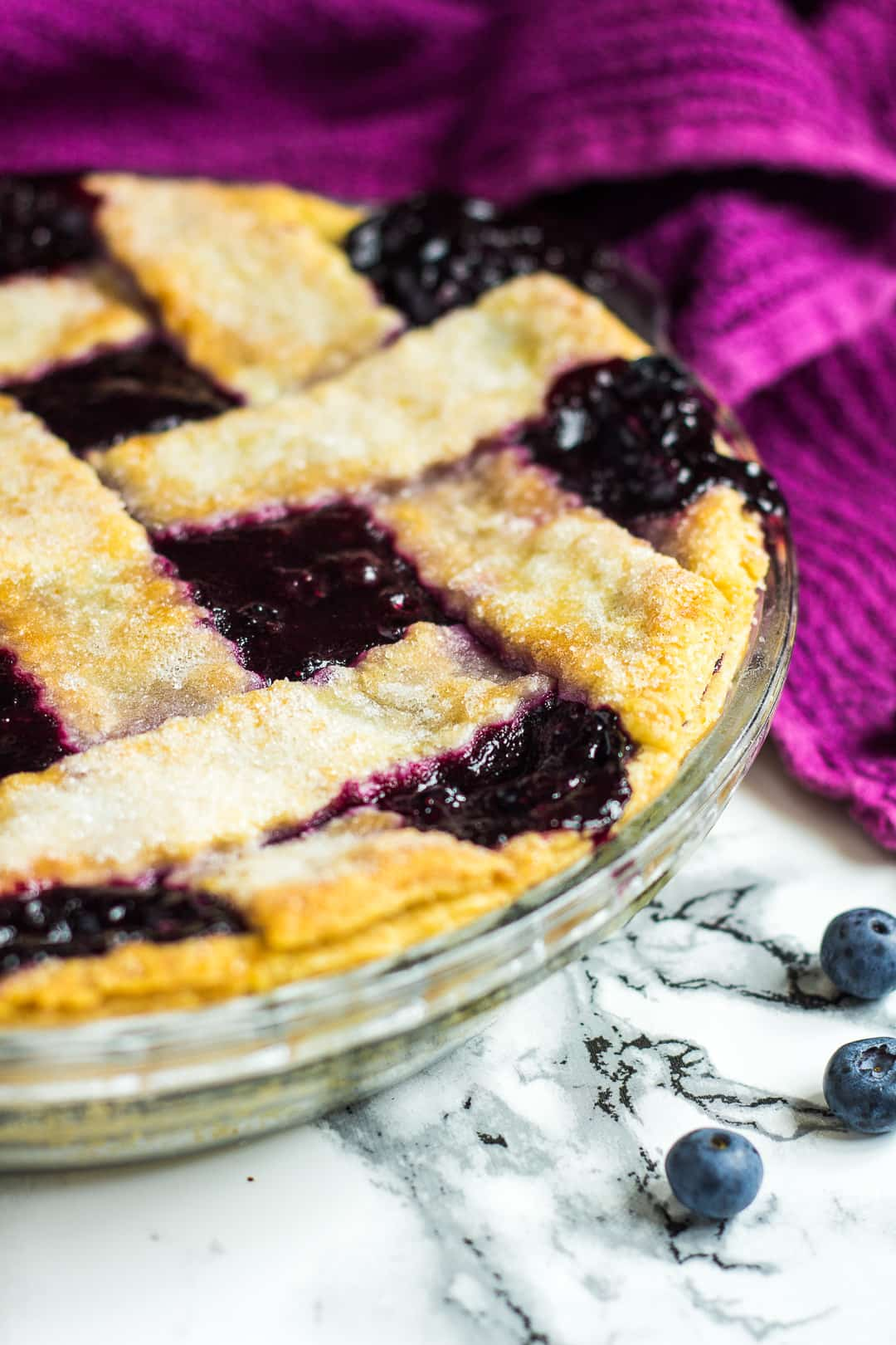 A homemade blueberry pie in a glass pie dish.