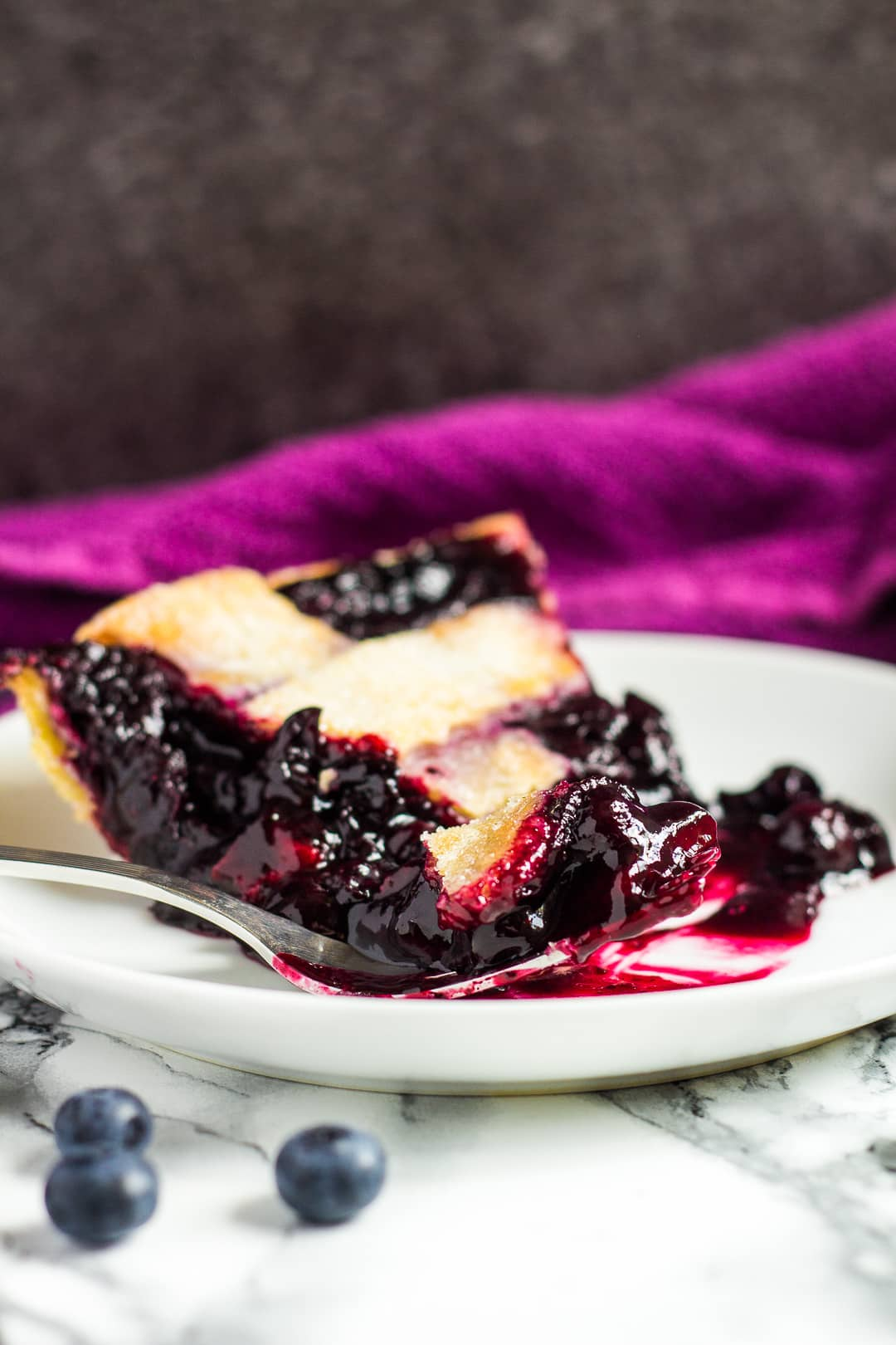 Slice of homemade blueberry pie served on a small white plate with a fork.