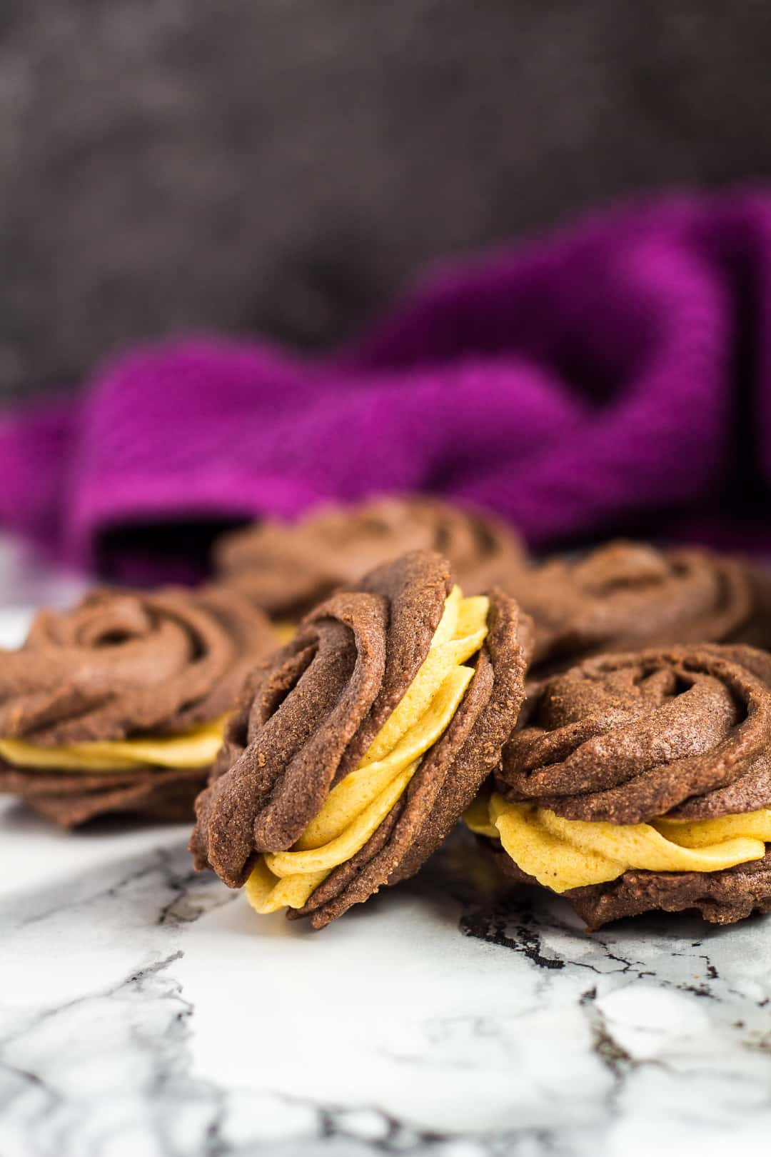 A pile of chocolate Viennese whirls filled with pumpkin buttercream.