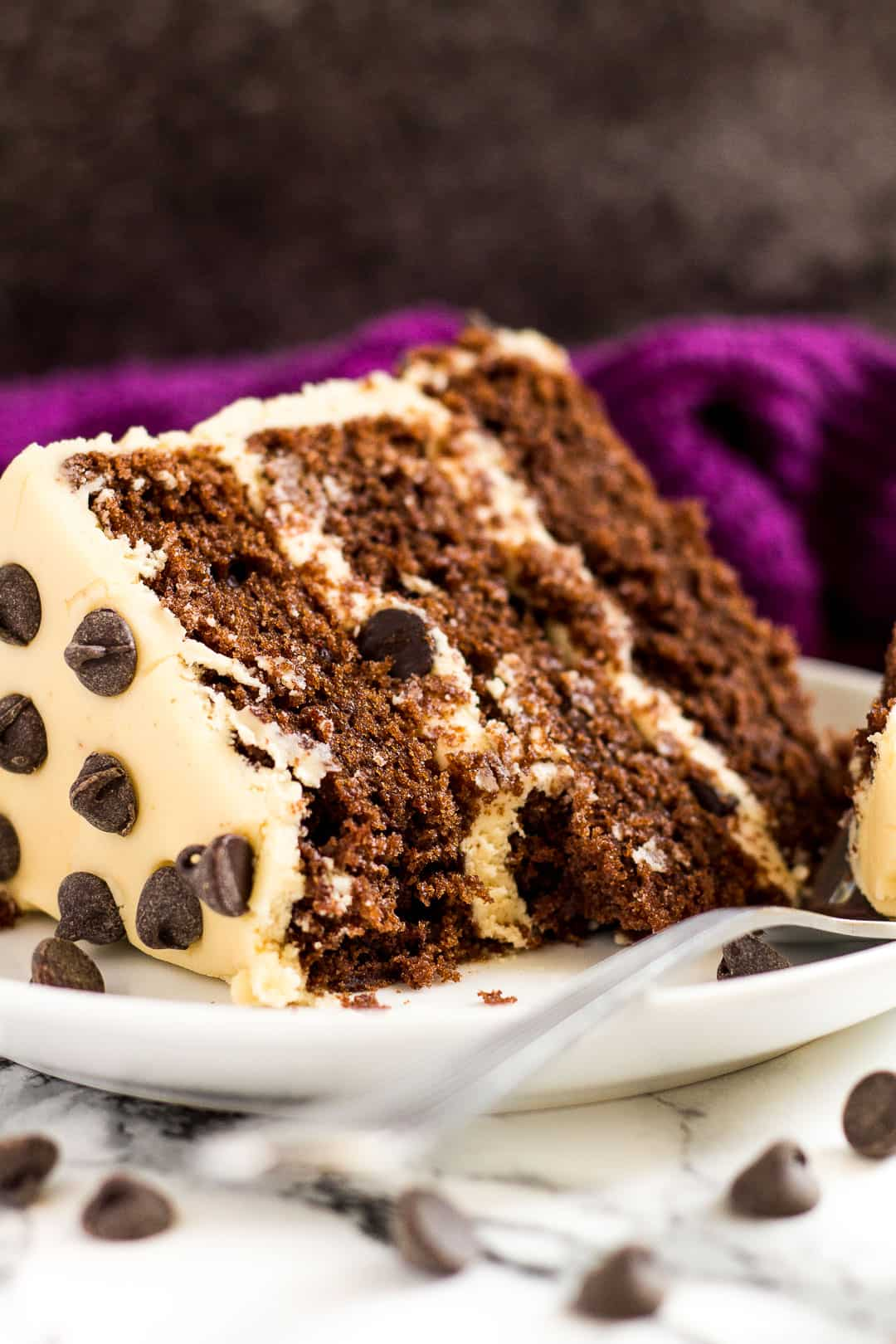 Slice of mocha layer cake on a small white plate with a fork.