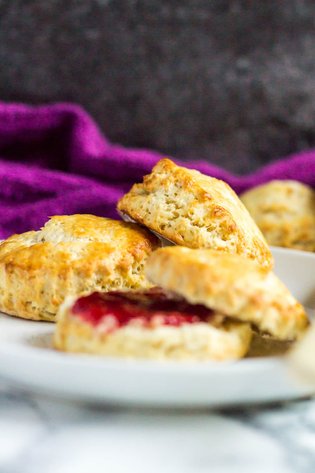 A sideview shot of a few Classic English Scones served on a small white plate. One scone is cut in half and filled with jam.
