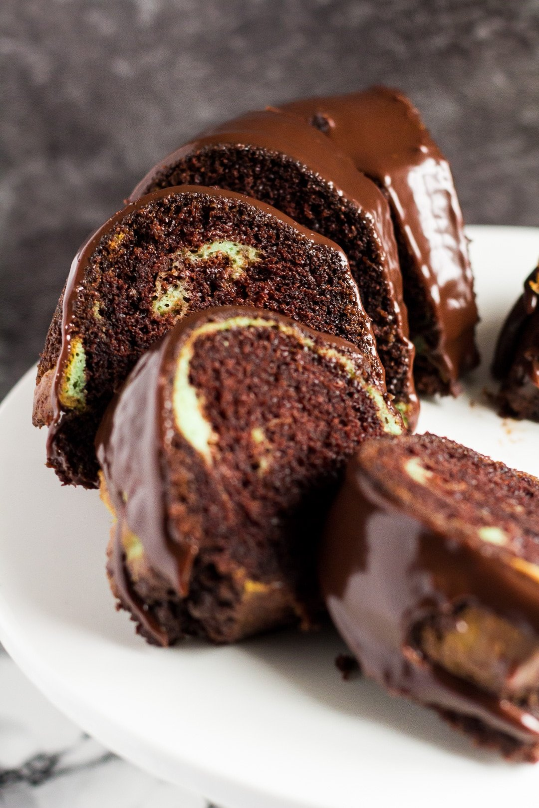 Slices of mint chocolate bundt cake served on a white cake stand.