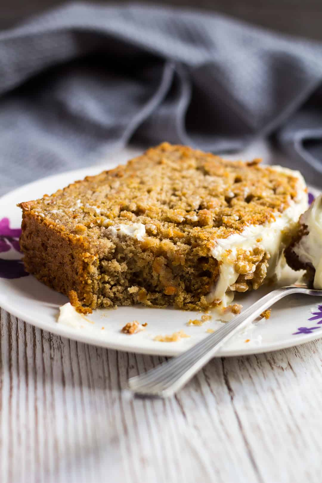A thick slice of Carrot Cake Loaf topped with cream cheese frosting served on a small white plate with a fork.