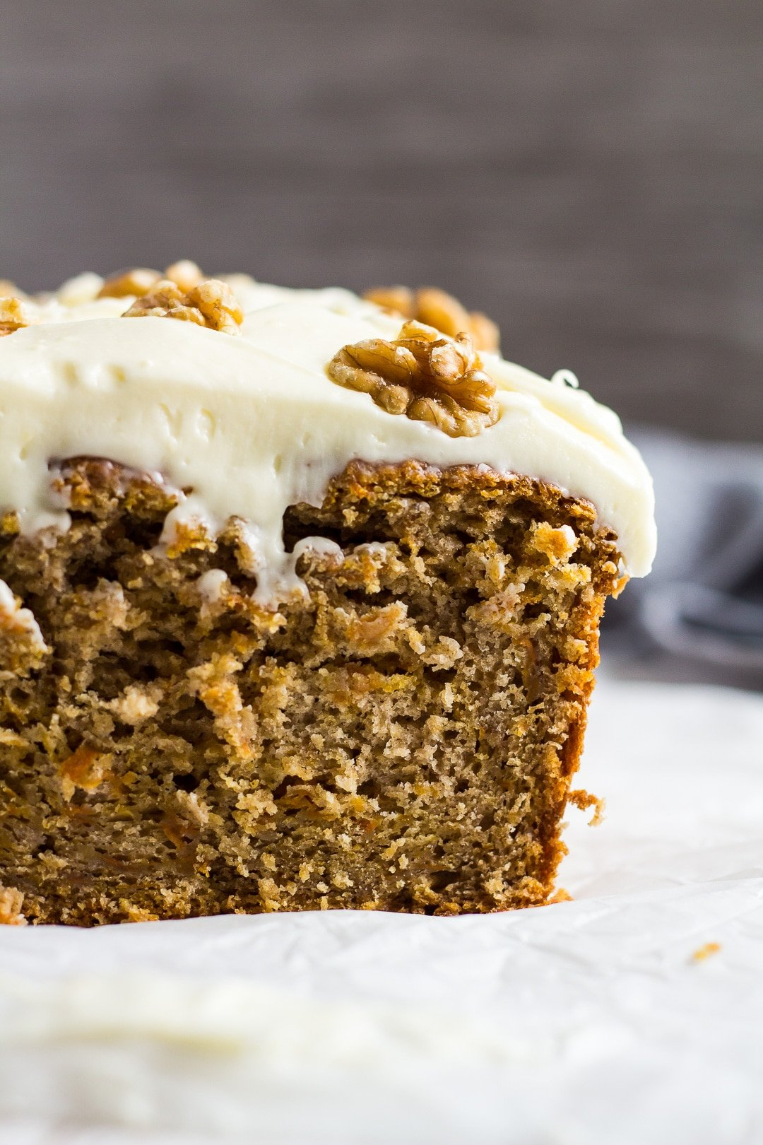A close-up shot of half a Carrot Cake Loaf topped with a thick layer of cream cheese frosting.