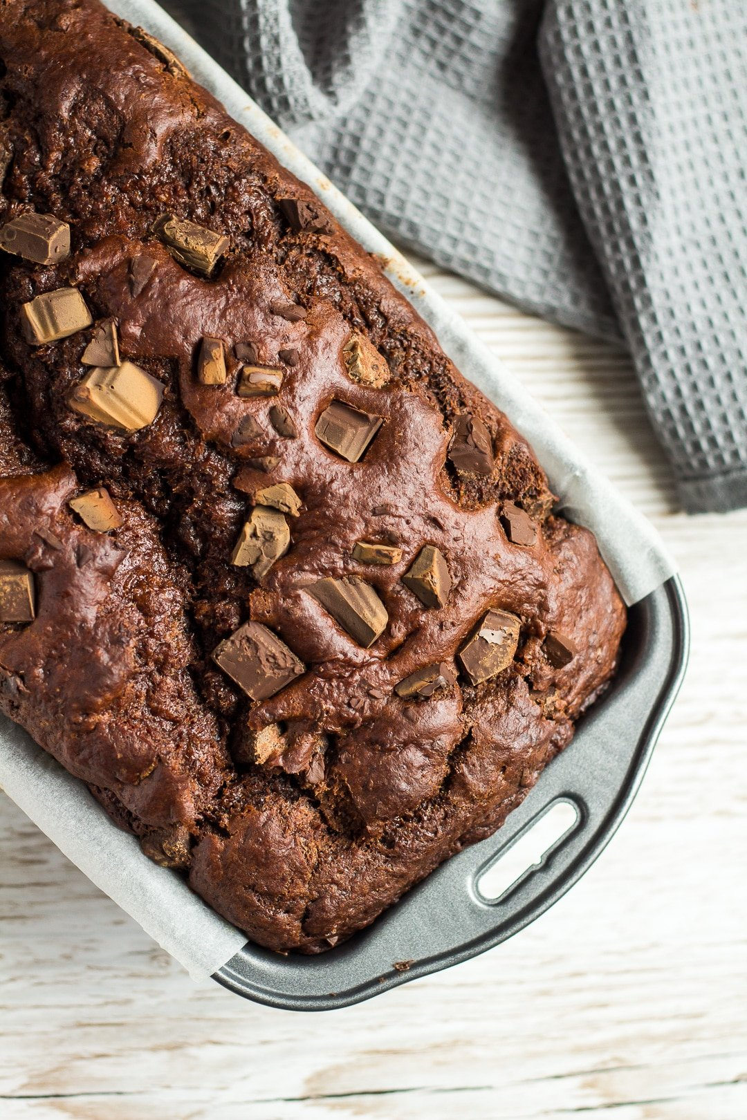 An overhead shot of Double Chocolate Banana Bread studded with chocolate chunks in a loaf pan.
