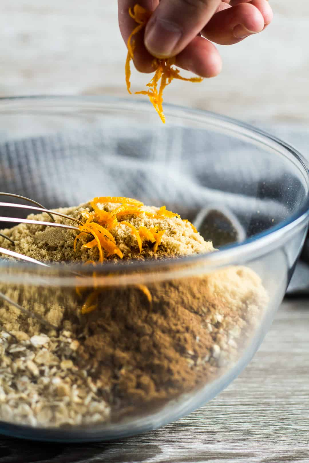 Orange zest being added to a glass mixing bowl full of ingredients for Hot Cross Bun Spiced Flapjacks.