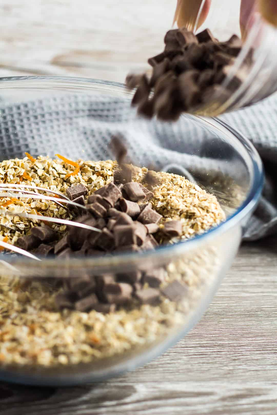 Chocolate chips being added to a glass mixing bowl of ingredients for Hot Cross Bun Spiced Flapjacks.