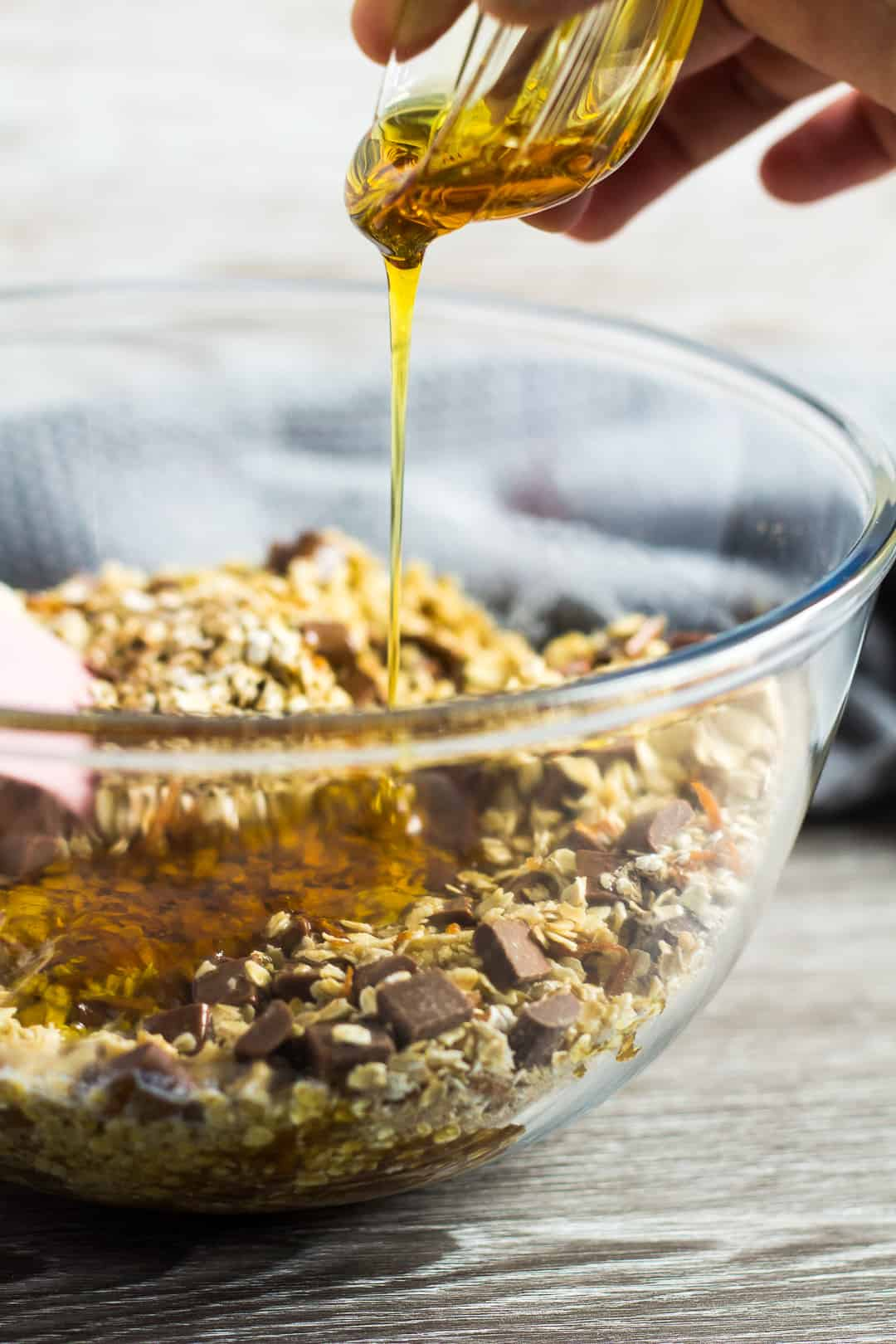 Golden syrup being poured into a glass mixing bowl of ingredients for Hot Cross Bun Spiced Flapjacks.