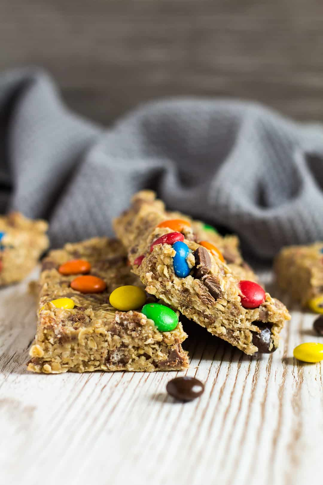 A sideview shot of two No-Bake Peanut Butter M&M Granola Bars overlapped.