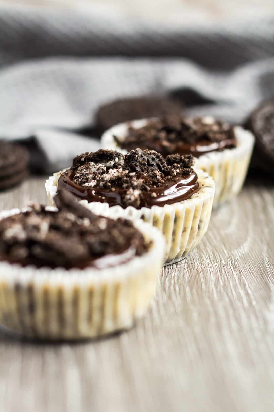 A row of three Mini Oreo Cheesecakes topped with chocolate ganache and crushed Oreos.