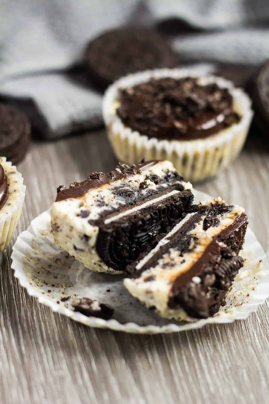 Mini Oreo Cheesecake cut in half in its wrapper to show whole Oreo crust.
