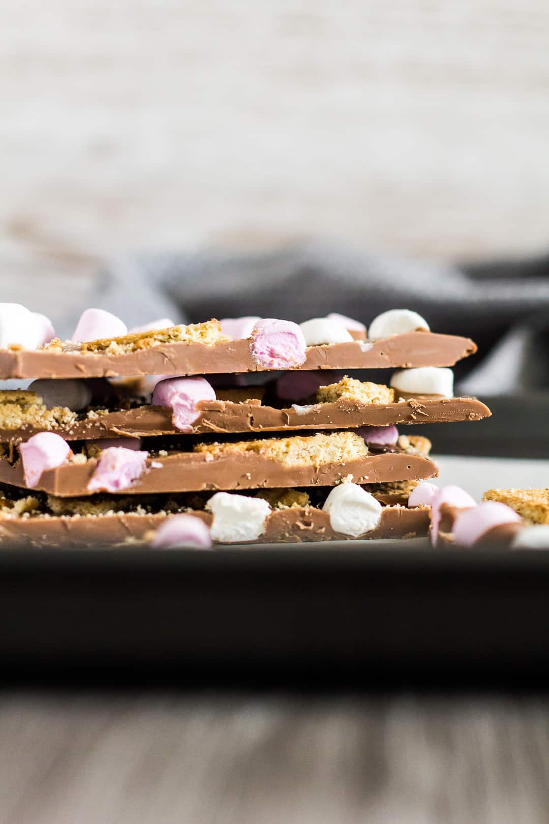 A stack of S'mores Chocolate Bark pieces on a baking tray.