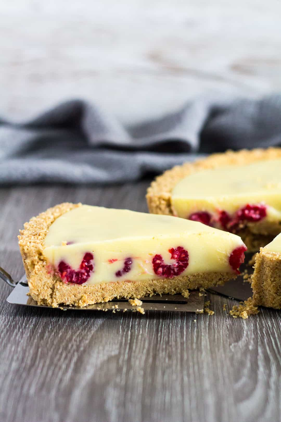 A slice being taken from White Chocolate Raspberry Tart.