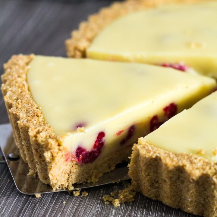 White Chocolate Raspberry Tart with slice being taken.