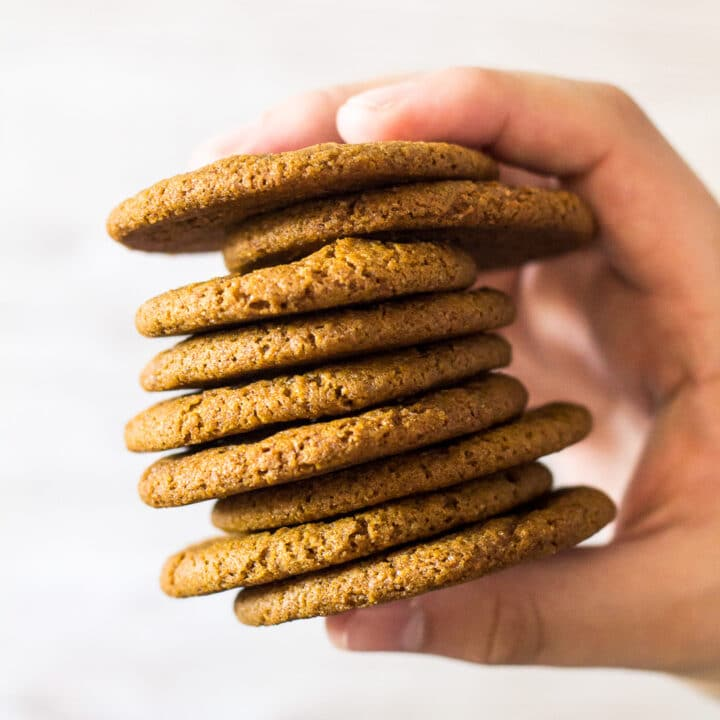A stack of Homemade Gingernut Cookies being held up by hand.