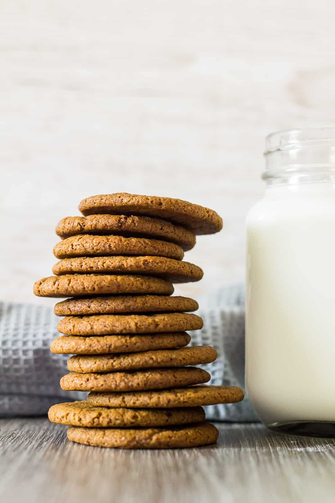 A tall stack of Homemade Gingernut Cookies next to a glass of milk.