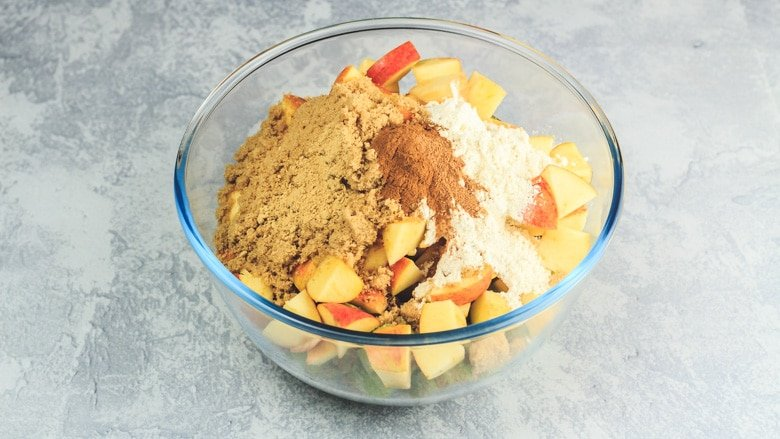 Rhubarb, apples, sugar, flour, and spices in a mixing bowl
