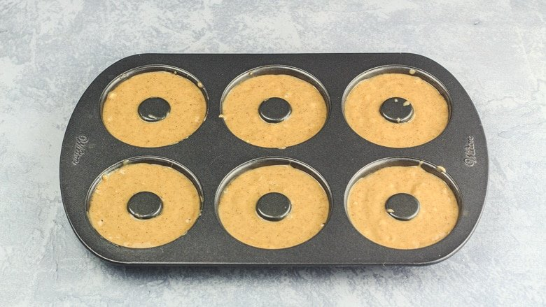 Apple Cider Doughnut batter in doughnut pan ready to be baked