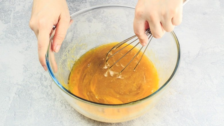 Whisking together wet ingredients in mixing bowl.