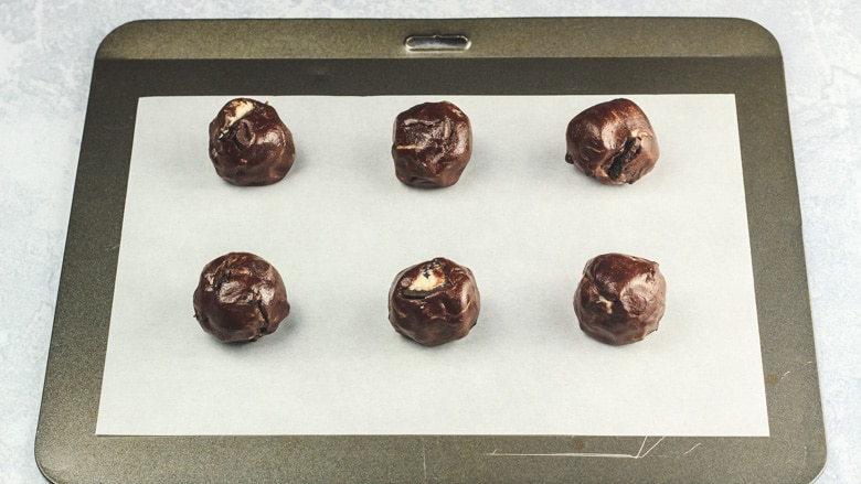 Chocolate Oreo cookie dough balls on baking tray ready to be baked.
