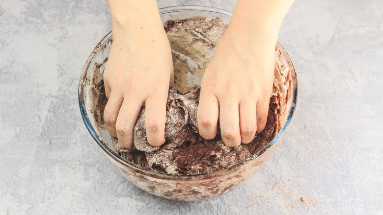 Mixing ingredients by hand to form a dough.