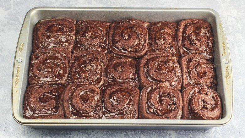 Chocolate cinnamon rolls in baking pan ready to be baked.