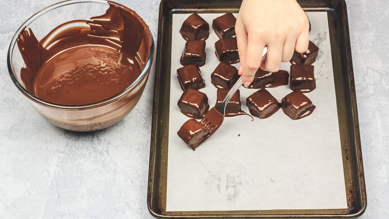Dipping brownie bites in chocolate and placing them on baking tray.