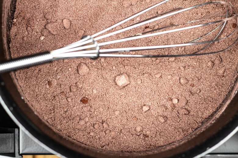Whisking together sugar, cocoa powder, cornflour, and salt in a saucepan.