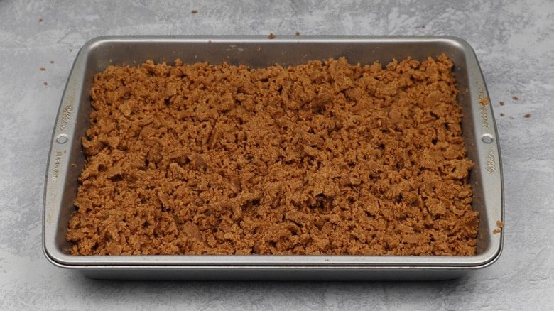 Crumb topping over cake batter in pan before baking.