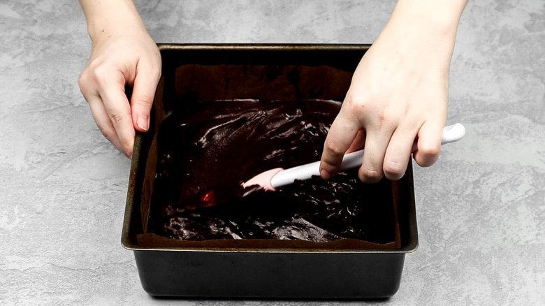 Spreading brownie batter out into baking pan.